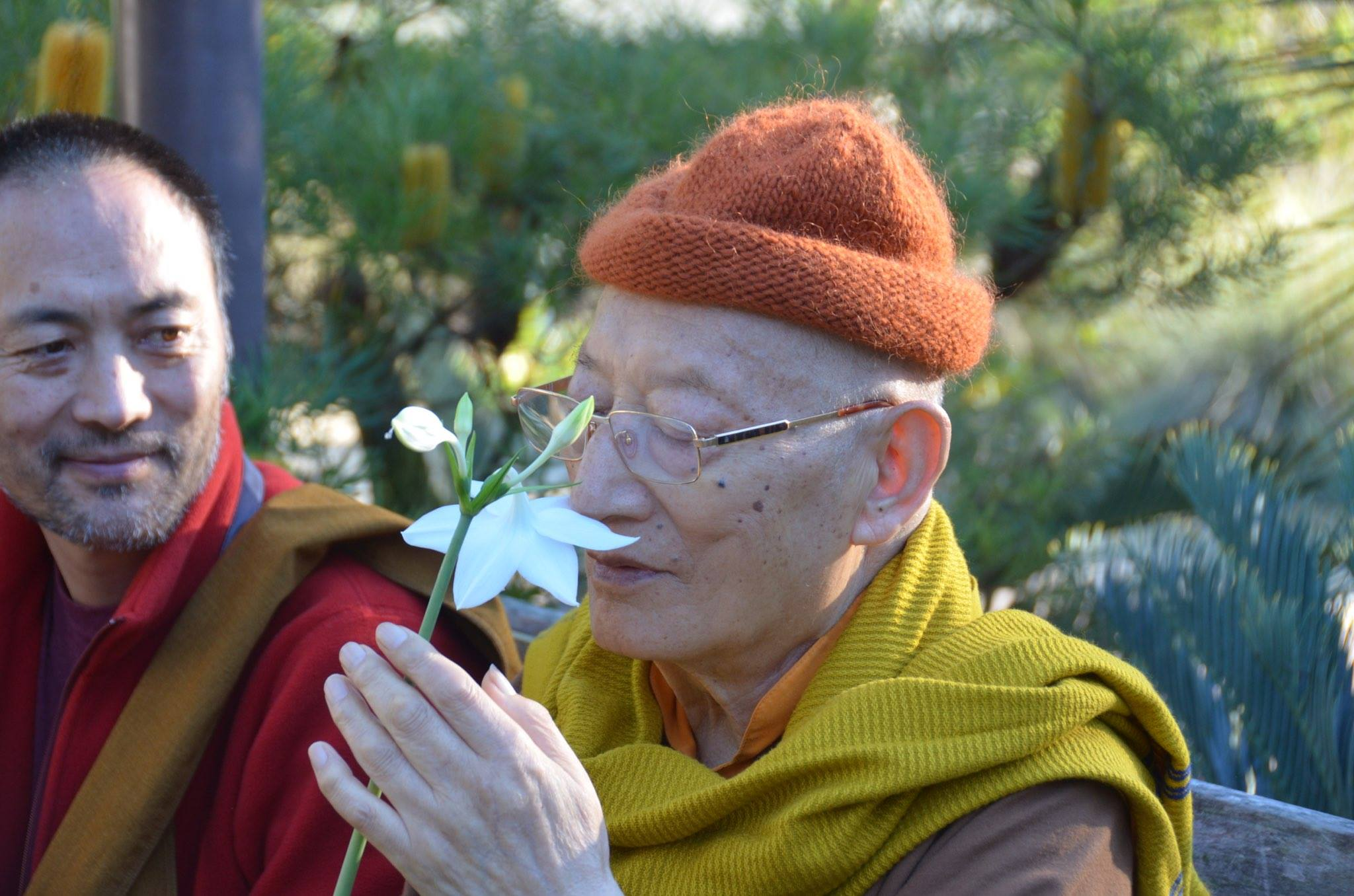 Khenche Rinpoche smelling a flower